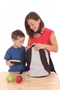 Gardienne prépare sac d'école d'un garçon
